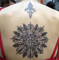 Amasing black pattern consisting of fleur de lis tattoo on back